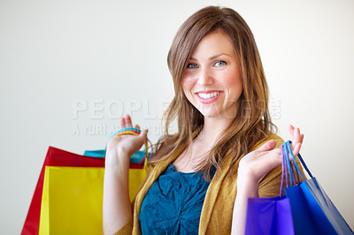 Buy stock photo Portrait of an attractive young woman holding her shopping bags with a smile
