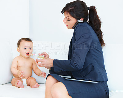 Buy stock photo Shot of a businesswoman trying to manage work and motherhood