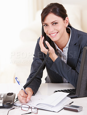 Buy stock photo Portrait of a confident businesswoman talking on the phone and taking notes
