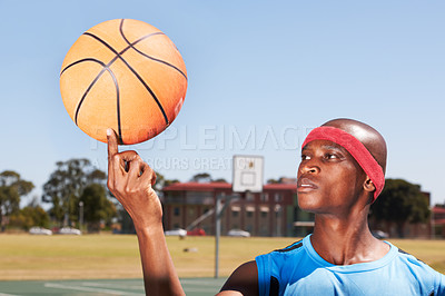 Buy stock photo A young sportsman balancing a basketball