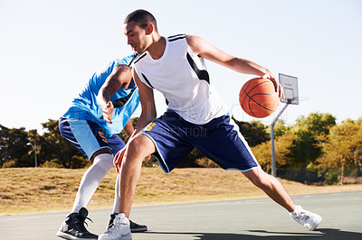 Buy stock photo Two basketball players playing a game of one on one
