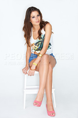 Buy stock photo Studio shot of an attractive woman dressed casually and sitting on a chair