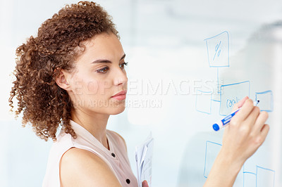 Buy stock photo A young businesswoman drawing up strategies