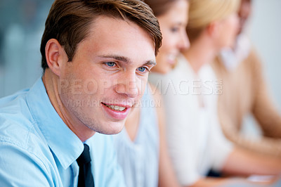 Buy stock photo A handsome young businessman listening to a colleague while brainstorming in the boardroom
