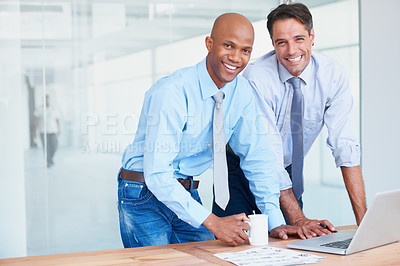 Buy stock photo Two co-workers smiling while working in the boardroom together