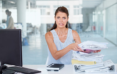Buy stock photo A stressed businesswoman grimacing and holding a pile of notes