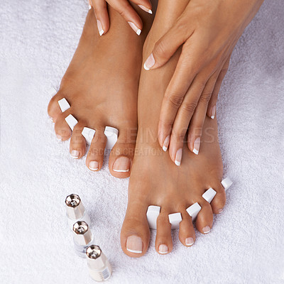 Buy stock photo Cropped view of hands touching perfectly pedicured feet with toe spacers and nail polish next to them