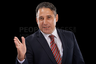 Buy stock photo A serious man in a suit gesturing with his hand while speaking