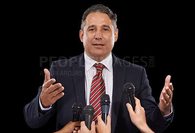 Buy stock photo Portrait of a mature man giving a press conference on a black background