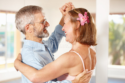 Buy stock photo Shot of a  mature couple dancing with one another in their home