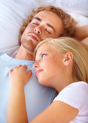 Buy stock photo A beautiful woman lying on her husband's chest while he sleeps