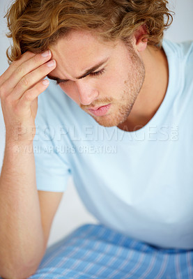 Buy stock photo A young man sitting iand looking very worried