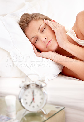 Buy stock photo A young woman massaging her temples while lying in bed with a headache