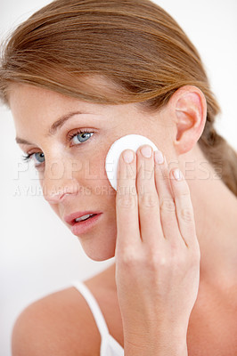 Buy stock photo A lovely young woman applying makeup to her cheek with a cotton pad