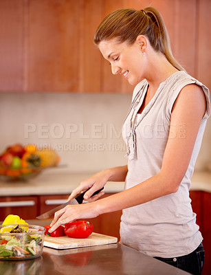 Buy stock photo A beautiful young woman slicing peppers for a salad in the kitchen