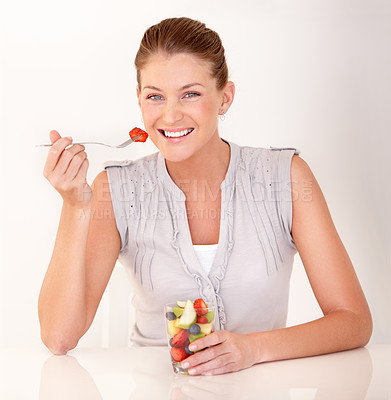 Buy stock photo A lovely young woman eating a healthy fruit salad