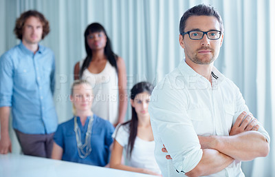 Buy stock photo Cropped shot of a businessman standing in front of his colleagues in the office