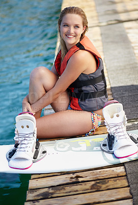 Buy stock photo A pretty young girl sitting on a jetty next to a wakeboard