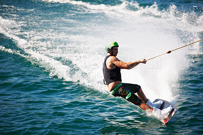 Buy stock photo A young man wearing a helmet and lifejacket wake boarding on a lake