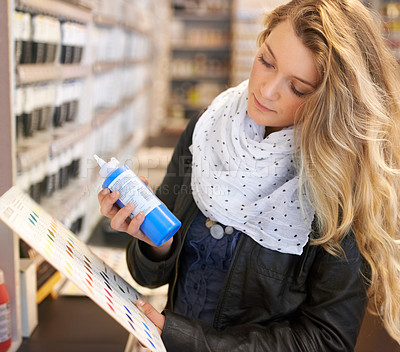 Buy stock photo Shot of a young female artist checking a colour chart in an art supplies store