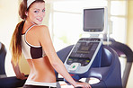 A beautiful young woman looking at you over her shoulder while using the treadmill