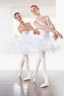 Buy stock photo Full length shot of two ballerinas rehearsing in a studio with a mirror behind them