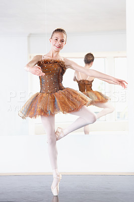Buy stock photo Shot of a ballerina rehearsing in a studio with her reflection in a mirror behind her