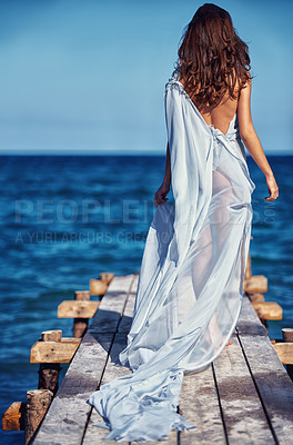 Buy stock photo Rear view of a young woman walking on a wharf