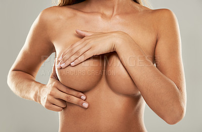 Buy stock photo Closeup studio shot of a topless woman examining her breasts against a gray background