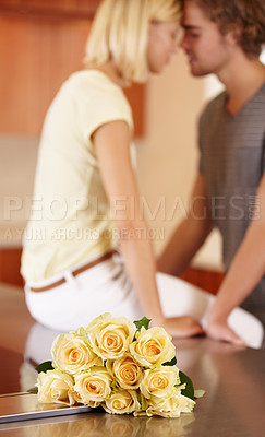 Buy stock photo A young couple kissing in the kitchen