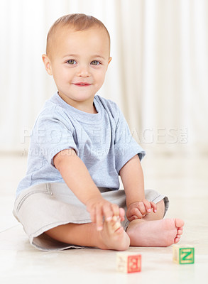 Buy stock photo Full length shot of a cute little boy playing at home with some wooden blocks
