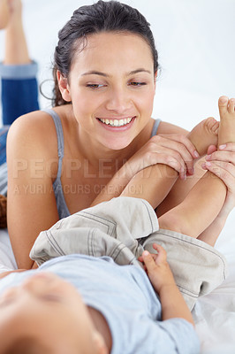 Buy stock photo An attractive young woman playing with her young son at home