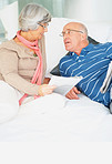 Senior man and woman holding newspapers while talking on bed