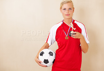 Buy stock photo Portrait of a young woman dressed in a soccer uniform holding up a trophy and a soccer ball