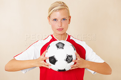 Buy stock photo Portrait of an attractive young woman holding a soccer ball