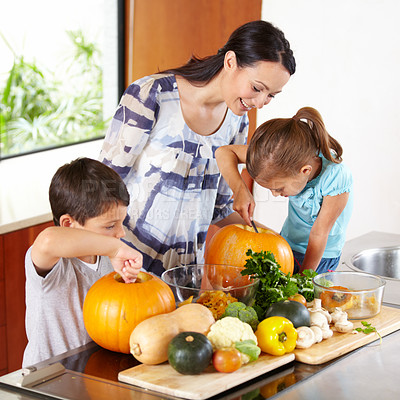 Buy stock photo Shot of a mother helping her children carve pumpkins for halloween