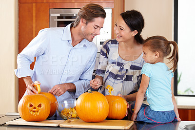 Buy stock photo A young mother and father standing with their young daughter in a kitchen preparing Jack O'lanterns for Halloween