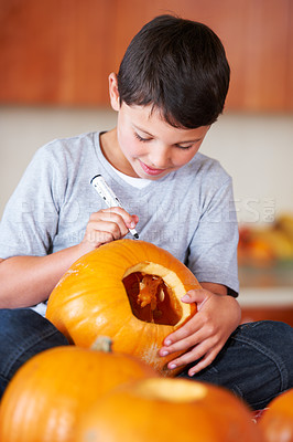 Buy stock photo A little boy sitting in the kitchen making a Jack O'lantern for Halloween