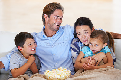 Buy stock photo Cute young family watching a movie together at home on the couch