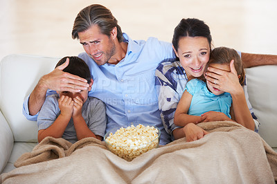 Buy stock photo Two parents covering their children's eyes while watching a scary movie