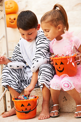 Buy stock photo Shot of two cute kids checking out their Halloween candy