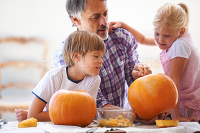 Buy stock photo A father and his two kids hollowing out pumpkins for halloween