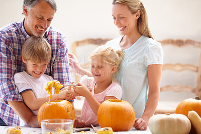 Buy stock photo A family of four carving pumpkins for halloween