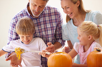 Buy stock photo A family of four carving pumpkins in the kitchen