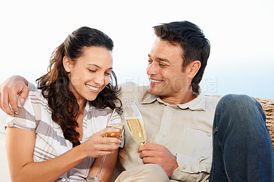 Buy stock photo A cute couple drinking champagne with the ocean in the background