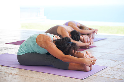 Buy stock photo Yoga instructor leading a class in stretching