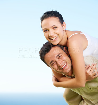 Buy stock photo A young man giving his girlfriend a piggyback with the ocean in the background