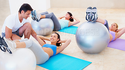 Buy stock photo Young woman doing a sit up during a pilates class with the help of an instructor