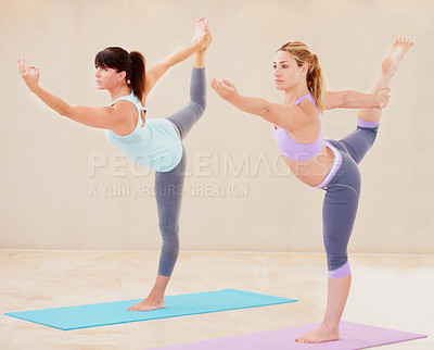 Buy stock photo Two skilled yoga enthusiasts working out together