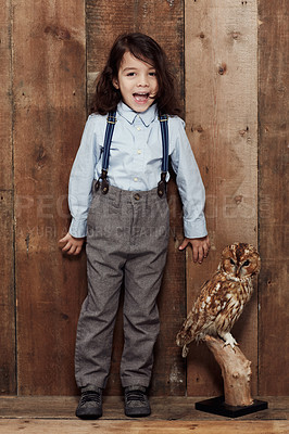 Buy stock photo Shot of a stylish young boy posing next to a stuffed owl